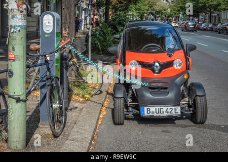 Berlin-Mitte. Renault Twizy electric car at charging point. Tiny two-seater car recharges battery in city street - Stock Photo