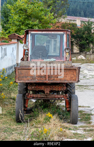 Old rusty tractor, on the street of the Ravnogor village in bulgaria. - Stock Photo