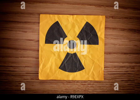 Radiation warning sign on a wooden board. Close up. - Stock Photo