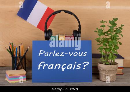 concept of learning French language - paper with text 'Parlez-vous français?' (Parlez vous francais?), flag of the France, books, headphones, pencils  - Stock Photo