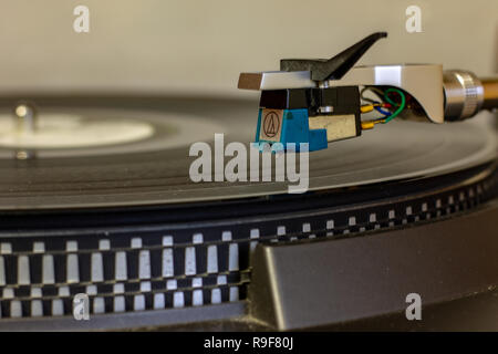 An old record player that still works and can read music from vinyl records. Famous its operation through the arm and the needle. - Stock Photo