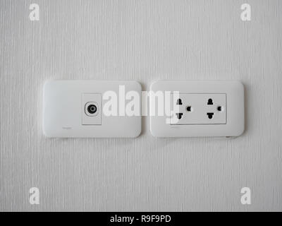 Plug Into Electricity Socket the power outlets on the wall. sockets plug outlets with 220 volts (220V) AC style. White electrical outlet on wall in th - Stock Photo