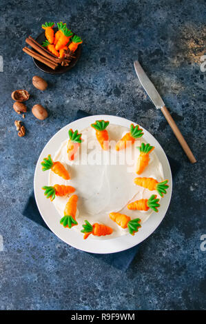 Carrot cake with cream cheese frosting decorated with carrot marmalade serving on a plate on a blue stone background. - Stock Photo