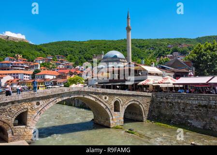 Stone bridge, Sinan Pasha Mosque and houses in the old town on the banks of the Prizren Bistrica River, Prizren, Kosovo - Stock Photo