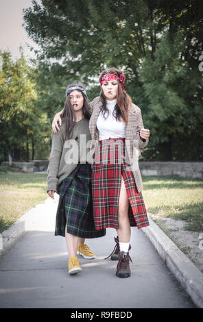 Two informally dressed girls walking down the street with cigarettes. Teenage problems. - Stock Photo