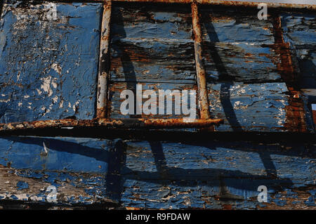 Watten, Hauts-de-France, France: peeling & flaking blue paint & orange rust on hull of old wooden fishing boat beside the canalised Aa river. - Stock Photo