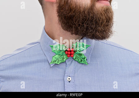 Close up of handsomely bearded office manager hipster with festive formal wear Christmas bow tie and blue shirt on white background. Christmas corpora - Stock Photo