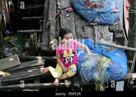 A little girl sitting on a wooden deck in a fishing village in Cambodia - Stock Photo