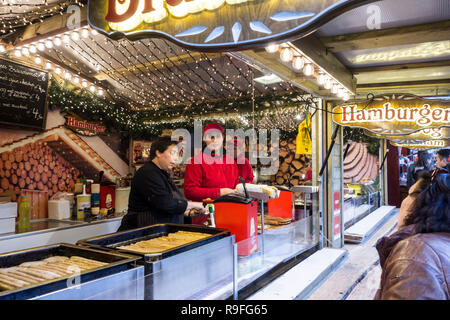 Street vendors in fastfood stand selling hot dogs at Christmas market in winter in the city Ghent, Flanders, Belgium - Stock Photo