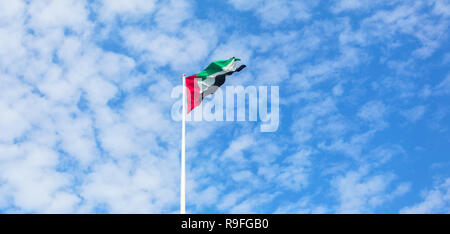 United Arab Emirates flag flying against beautiful blue sky with clouds. UAE celebrates it's national day on 2nd December every year. - Stock Photo