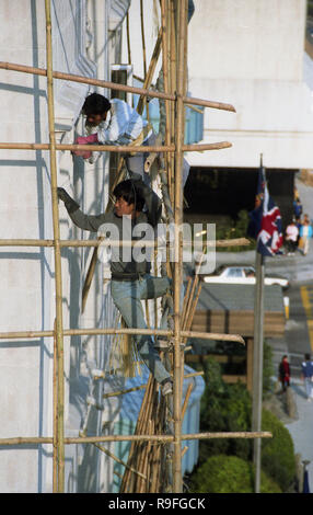1980s, workers putting up bamboo scaffolding high-up outside a tall building in Hong Kong. A traditional chinese method of scaffolding, this ancient trade involves much skill and intelligence to build platforms strong enough to take the weight of construction workers. Hong Kong is known as the last frontier of this type of scaffolding which is both cheaper and less destructive than its metal alternative. - Stock Photo