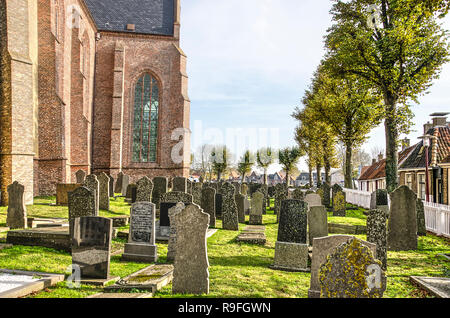 Workum, The Netherlands, November 4, 2018: view of the churchyard, flanked by late-gothic Saint Gertrudis church - Stock Photo