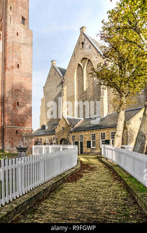 Workum, The Netherlands, November 4, 2018: footbath, lined with white fences, between the tower and the nave of Saint Gertrudis church - Stock Photo