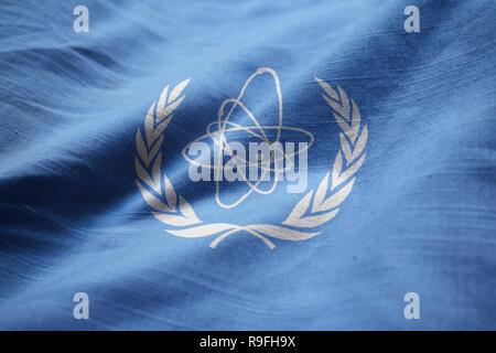 Closeup of Ruffled International Atomic Energy Agency Flag, IAEA Flag Blowing in Wind - Stock Photo