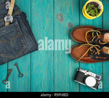 Travel concept - shoes, jeans, camera, watch and vintage keys on the blue wooden desk - Stock Photo