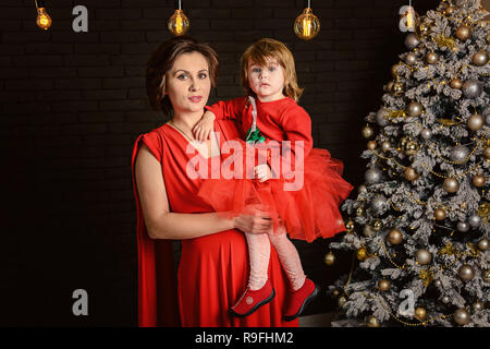 Happy young mother holds on the hands her cute baby girl on Christmas and New year holidays Child with mom in red dresses in the decorated room with C - Stock Photo