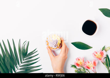 Flat lay composition woman's hand holding cupcake with cream on white table next to cup of coffee and flowers, top view. - Stock Photo