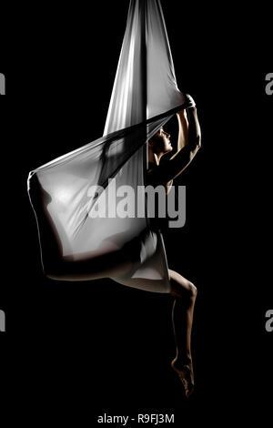 female posing aerial anti-gravity yoga on a hammock - Stock Photo