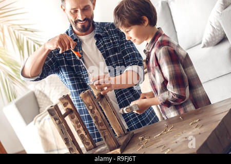 Father and little son together at home standing at table dad screwing screw into chair leg smiling cheerful while boy holding hammer looking curious a - Stock Photo