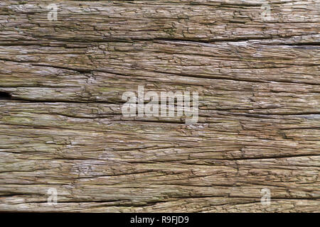 The texture of the old wooden board with deep grooves, faded in the rain and sun in the open air. Daylight. Close-up - Stock Photo
