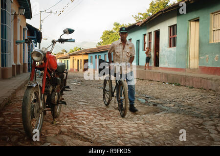 Man passing by with his bicycle, and a vintage motorbike, on the cobbled streets of Trinidad, Cuba - Stock Photo