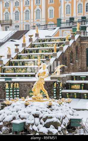 SAINT PETERSBURG, RUSSIA - JANUARY 22, 2018: Peterhof in winter. Statue of Samson, tearing the jaws of lion, against background of the Grand Cascade c - Stock Photo
