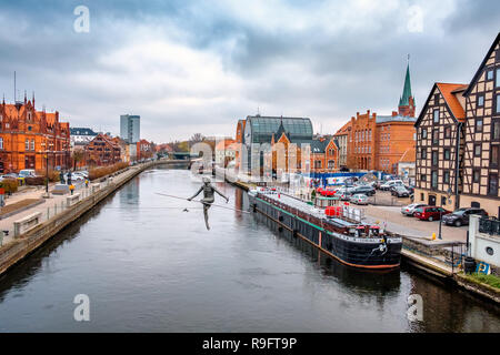 BYDGOSZCZ, POLAND, NOVEMBER 25, 2018: Embankment of the Polish city of Bydgoszcz in autumn, statue 'Crossing the River', view from the bridge over the - Stock Photo