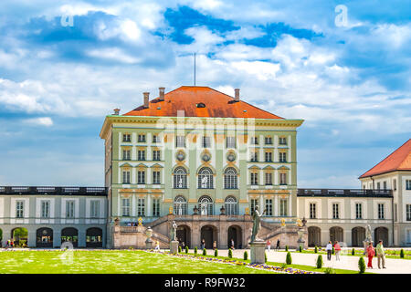 Great back view of the central pavilion of Munich's famous Nymphenburg Palace. Visitors enjoy a stroll in the Grand Parterre of the baroque palace. - Stock Photo