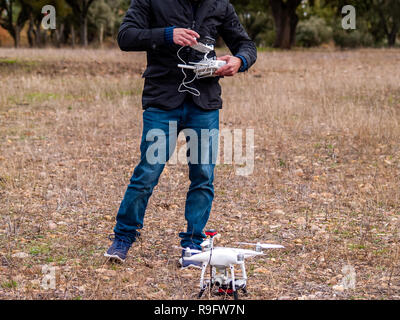 A drone pilot configuring his drone in the forest before flying - Stock Photo