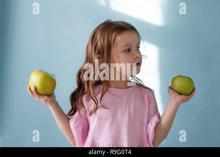 small beautiful girl eating fresh fruit Green Apple - Stock Photo