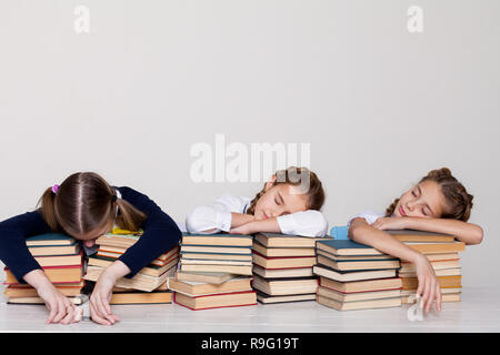 three girls in the classroom are tired of sleeping on books - Stock Photo