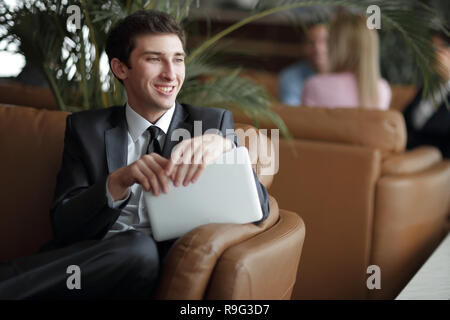 close-up of a young businessman using a digital tablet sitting in the lobby of the Bank - Stock Photo