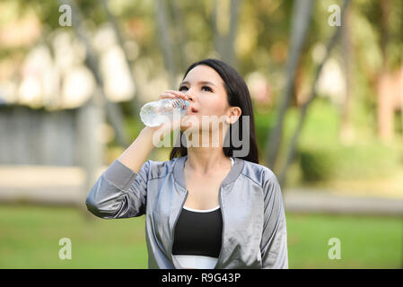 woman drinking water bottle health concept / smiling young girl relax exercise and hold water bottle for drinking water in hand on outdoor happy woman - Stock Photo