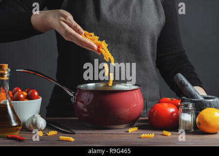 Cooking italian pasta in a pot in the kitchen, Chef preparing food, meal. The woman-the cook throws into the pot the pasta fusilli. - Stock Photo