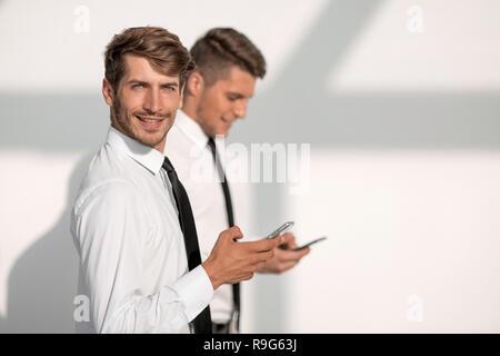 Businessmans holding mobile phone - Stock Photo