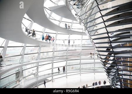 Visitors inside the glass dome on the top of Reichstag Building, a seat of the German Parliament (Deutscher Bundestag) and popular tourist attraction  - Stock Photo
