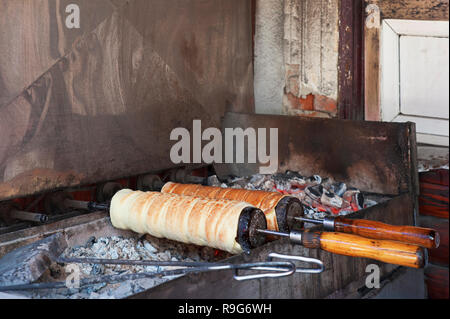 Kurtoskalacs, a spit cake traditional to Transylvania region, baking on hot charcoal at a typical open air market street bakers in Bran, Romania - Stock Photo