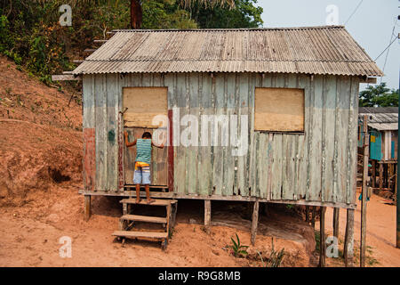 Boca de valeria, Brazil - December 03, 2015: hut on piles and boy child in village on mud background. Poverty and childhood concept. - Stock Photo