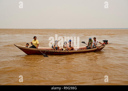 Boca de valeria, Brazil - December 03, 2015: people rowing in boat on brown water surface on grey sky. Travel and travelling concept. - Stock Photo