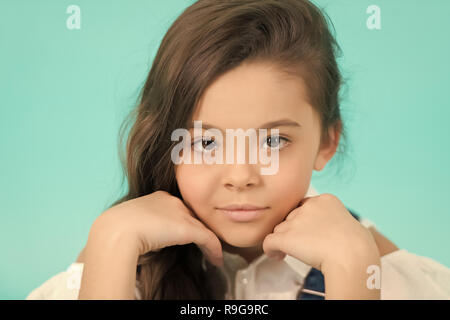 Child with on adorable face on blue background. Little girl pose with hands at young healthy face skin. Skincare, health, youth. Beauty, look, hairstyle, punchy pastel - Stock Photo