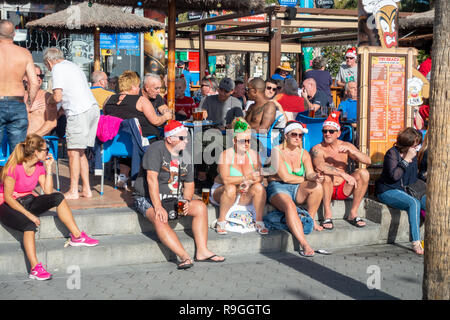 Benidorm, Costa Blanca, Spain, 24th December 2018. British holidaymakers escaping from the cold weather back home flood this popular resort during the Christmas holidays. Drinkers enjoy the hot temps and calm weather at the famous Tiki Beach Bar on Levante beach today in Benidorm on the Costa Blanca coast. Temperatures were in the mid to high 20's Celsius today in this Mediterranean hotspot. Credit: Mick Flynn/Alamy Live News - Stock Photo