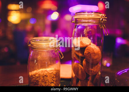 Desserts choice. Cookies and biscuits in glass jars on counter bar for sale. Chocolate drops and chips, oatmeal cookies stacks - Stock Photo