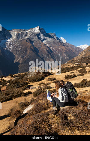 Np893 Nepal, Namche Bazar, couple looking at map opposite Kongde Ri, on path up to Namche Bazaar airfield - Stock Photo
