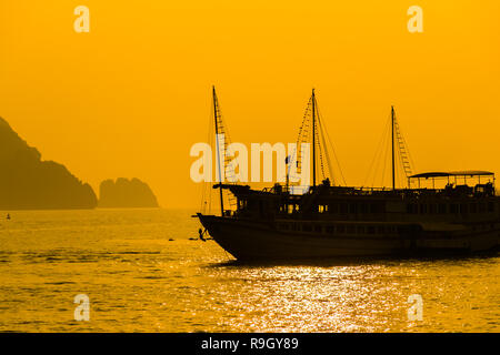 Silhouette Sunset Boat, Halong Bay in Vietnam - Stock Photo