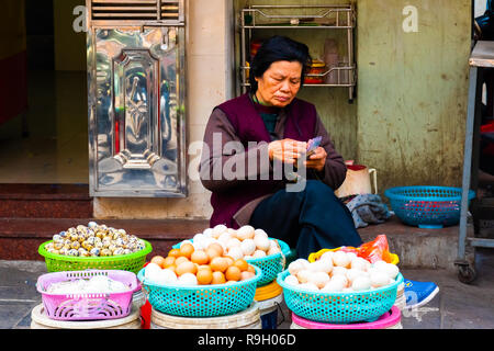 HANOI, VIETNAM - Feb 13, 2018: A woman selling eggs at a Old street market in Hanoi, Vietnam. - Stock Photo
