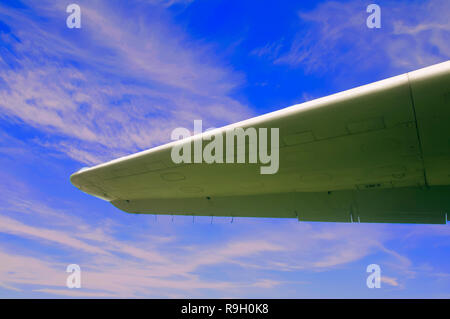 Aircraft wing on the blue sky background, summer - Stock Photo