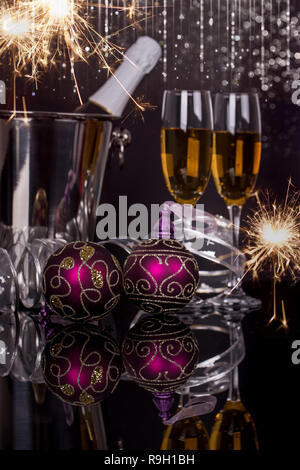 Two wine glasses with champagne, bottle in bucket, sparklers and Christmas ornaments on a black background. Copy space. Merry Christmas and Happy New  - Stock Photo