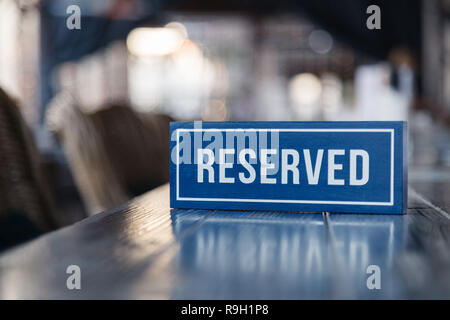 Closeup wooden blue white rectangular plate with the word Reserved standing on gray table in restaurant. Сoncept of preparation for the banquet, close - Stock Photo