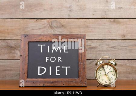 Alarm clock and blackboard with text 'Time for diet'' on brown wooden background - Stock Photo