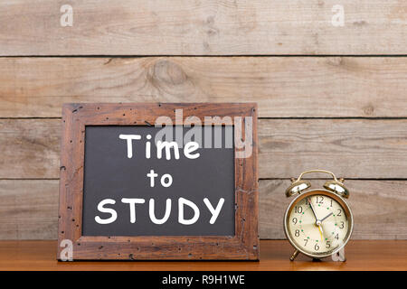 Alarm clock and blackboard with text 'Time to study'' on brown wooden background - Stock Photo